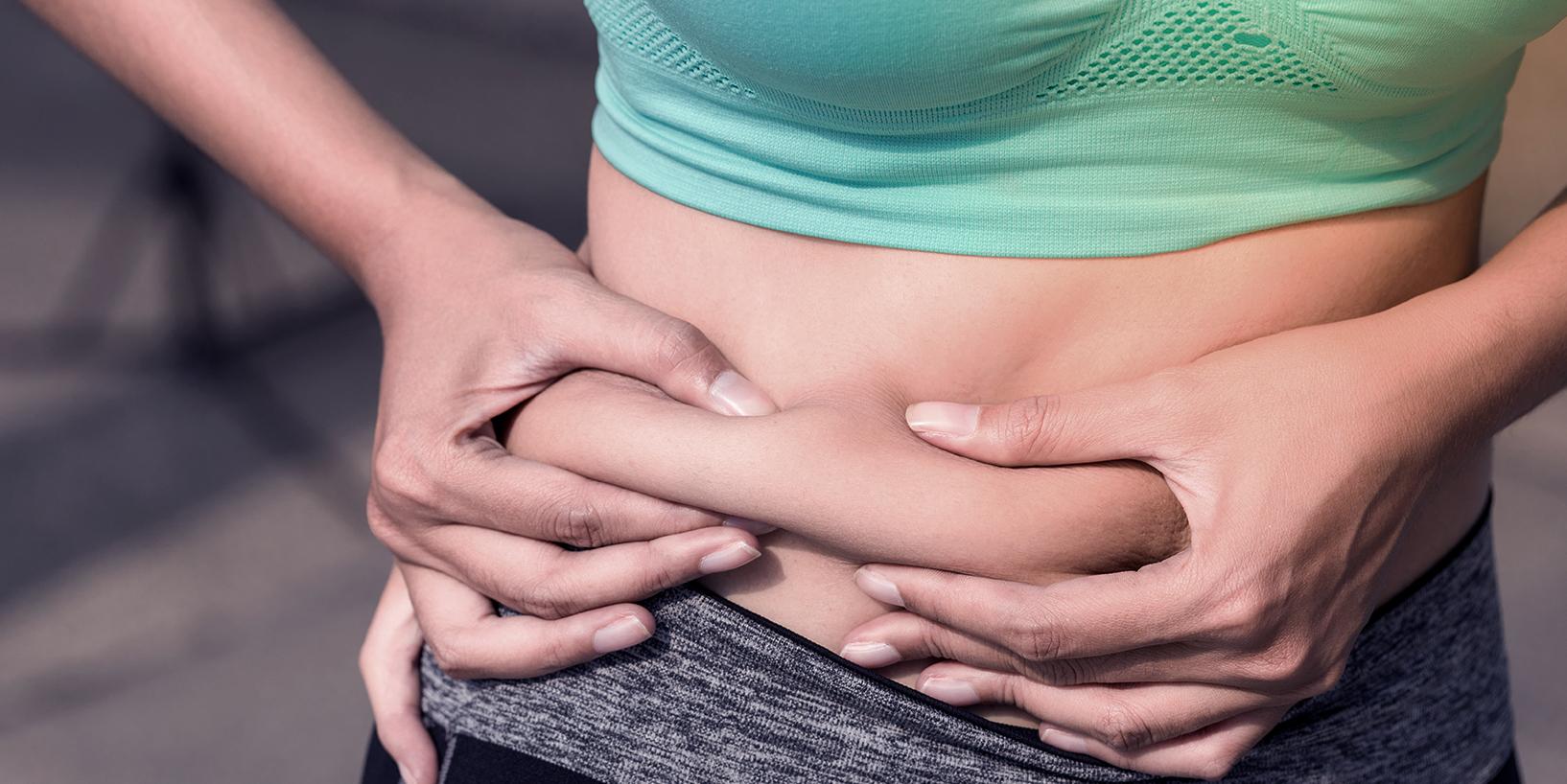 Photograph of woman grabbing slight stubborn belly fat
