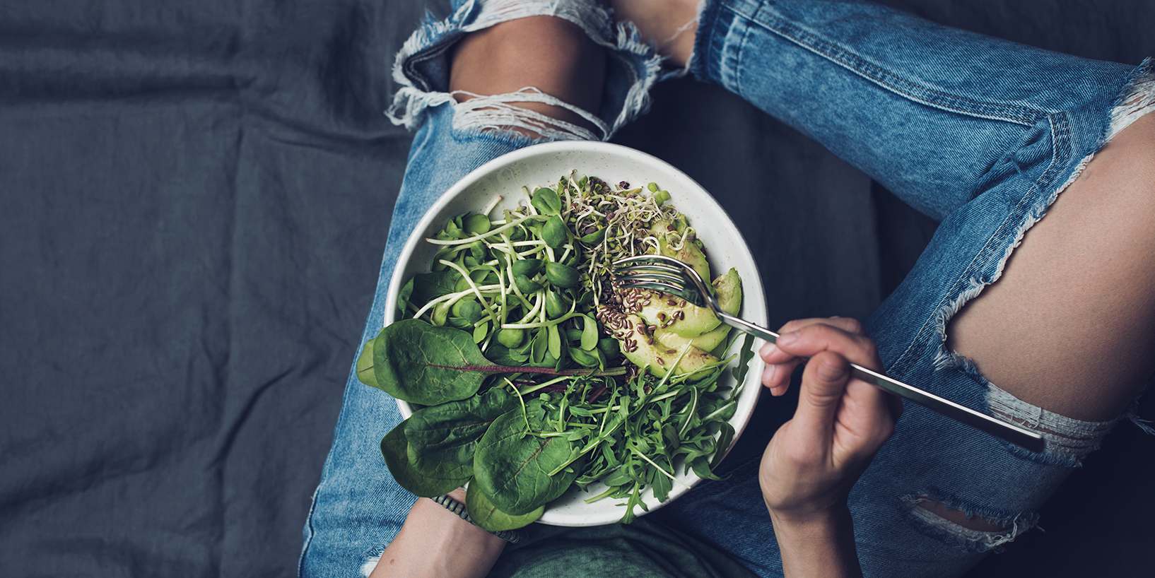 woman with ripped jeans eating a healthy salad with healthy fats like avocados